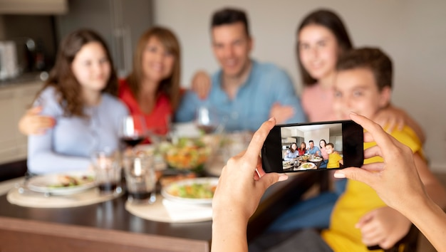 Pessoa tirando foto de família na hora do jantar Foto gratuita