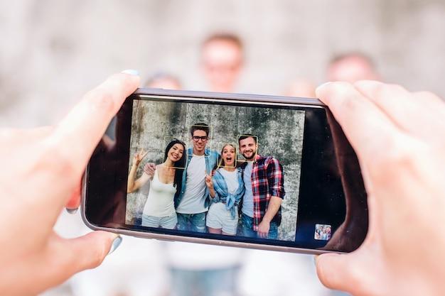 Pessoa tirando foto de quatro pessoas felizes