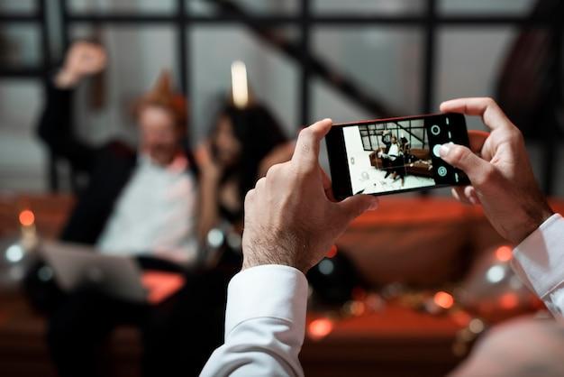 Pessoa tirando uma foto de seus amigos na festa de ano novo
