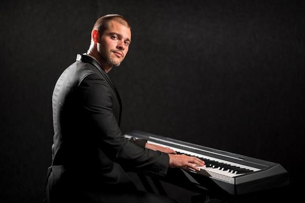 Pessoa tocando piano digital no estúdio