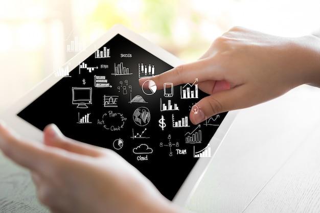 Pessoa tocar em um tablet e gráficos que vem de fora