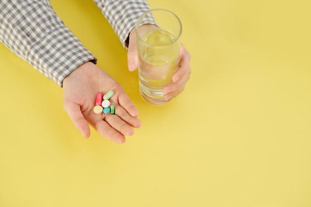 Pessoa tomando um punhado de comprimidos, comprimido e copo d'água