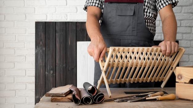 Pessoa trabalhando em um objeto de madeira com espaço de cópia