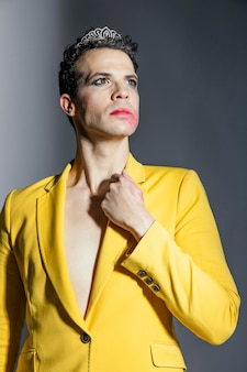 Pessoa trans usando jaqueta amarela e maquiagem