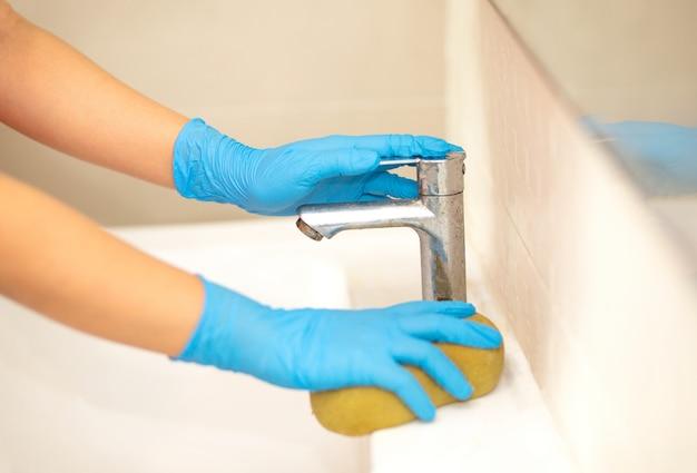 Pessoa, uma mão em uma luva de borracha azul na foto, remove e lava a pia do banheiro