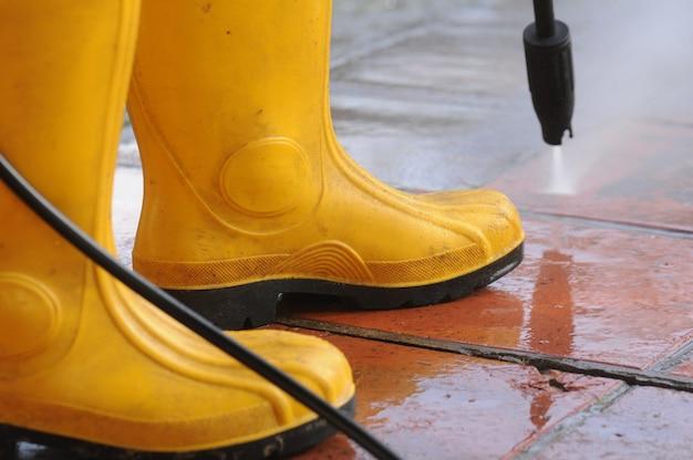 Pessoa usando botas de borracha amarela com bocal de água de alta pressão, limpando a sujeira nos ladrilhos