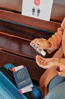 Pessoa usando desinfetante para as mãos ao lado da bagagem e passaporte de saúde