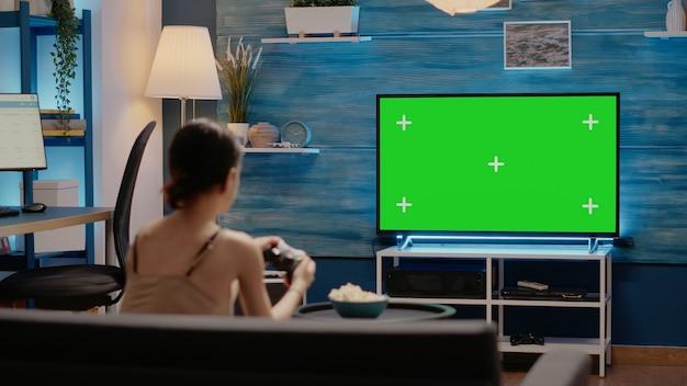 Pessoa usando joystick e tela verde na tv