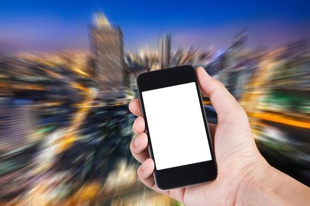 Pessoa usando o suporte de tela branca do smartphone na mão com fundo embaçado da grande cidade vista superior.