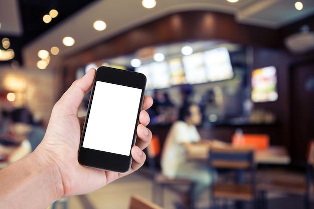Pessoa usando o suporte de tela branca do smartphone na mão com o fundo borrado do café.