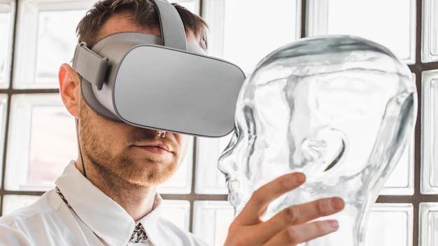 Pessoa, usando óculos de realidade virtual, segurando um manequim transparente