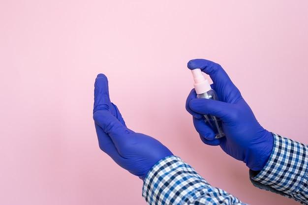 Pessoa, usando, pequeno, portátil, antibacteriano, mão, desinfetante, mãos, isolado, ligado, rosa, luvas azuis, ligado, mãos