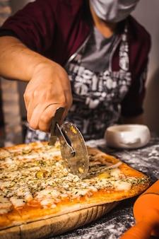 Pessoa usando uma máscara e cortando uma pizza no meio
