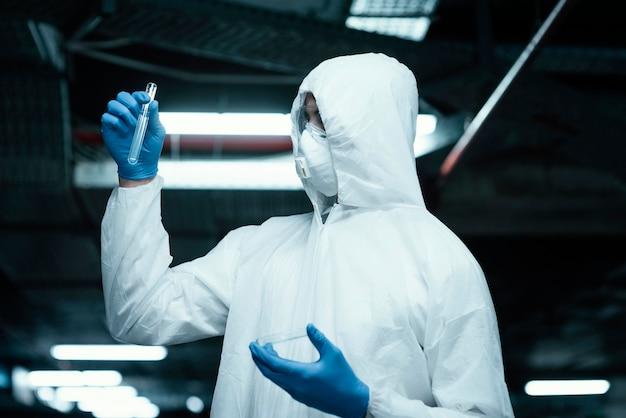 Pessoa vestindo uma roupa de prevenção enquanto coleta amostras