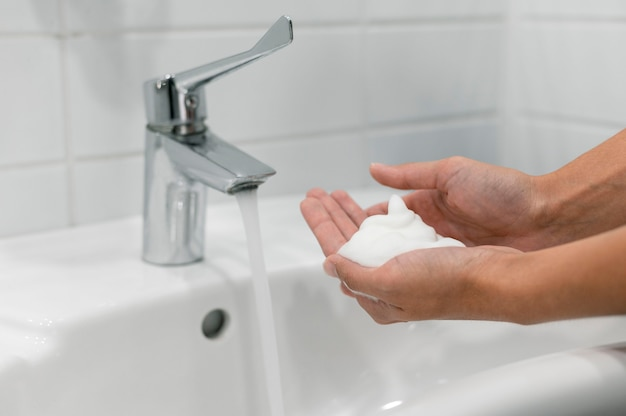 Pessoa vista lateral lavando as mãos com sabonete