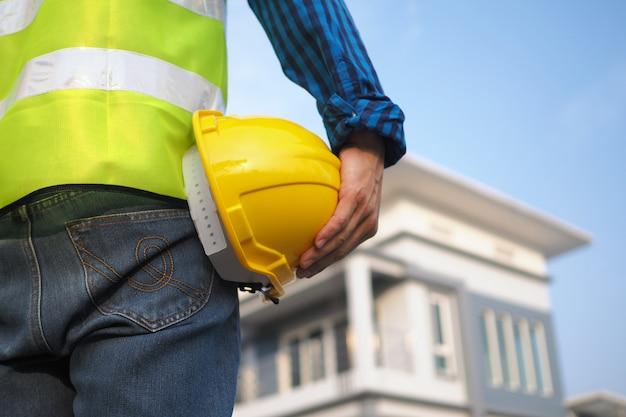 Pessoal construção, segurando, um, chapéu duro, com, um, externo, casa, construído