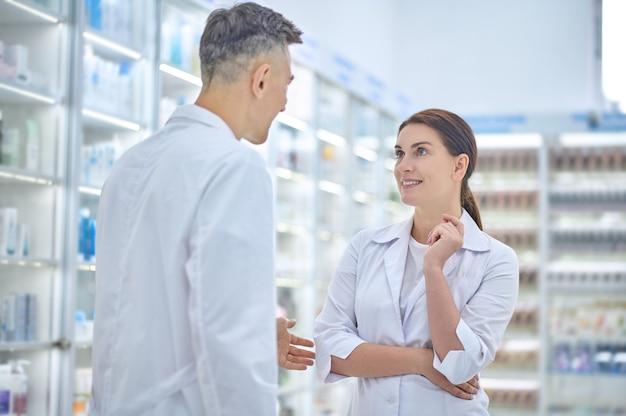 Pessoal, farmácia. jovem adulto e mulher em jalecos brancos em pé, frente a frente, conversando no corredor da farmácia