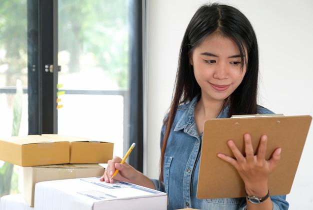 Pessoal feminino, mantendo os arquivos na mão, verificando o pacote.