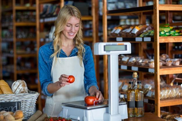 Pessoal feminino pesando legumes em escala