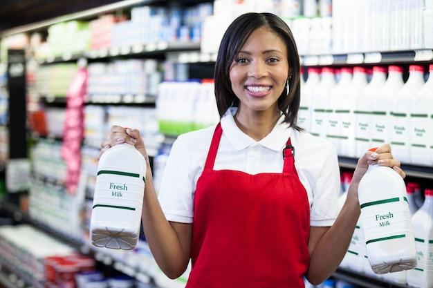 Pessoal feminino segurando garrafas de leite na prateleira