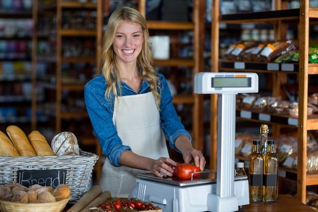Pessoal feminino sorridente pesando legumes em escala no supermercado