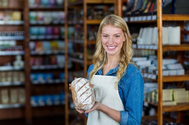 Pessoal feminino sorridente segurando pão no supermercado