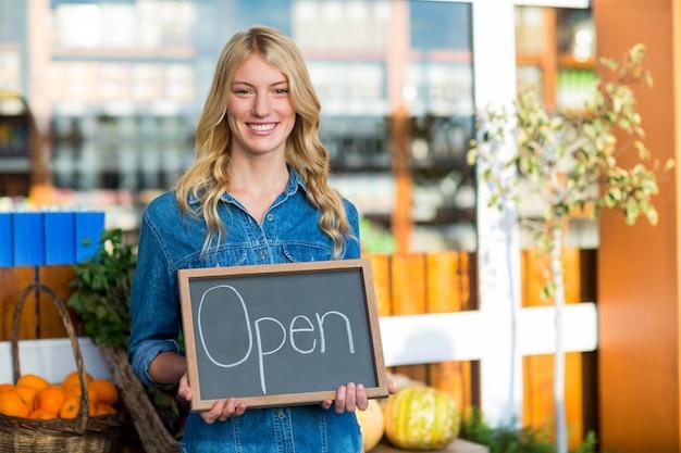 Pessoal feminino sorridente segurando placa de sinal aberto no super mercado