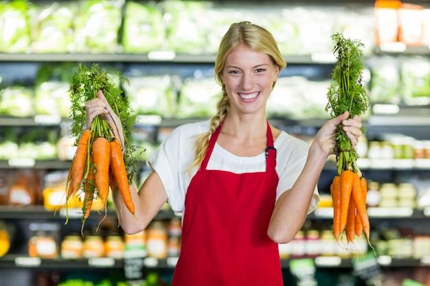 Pessoal feminino sorridente segurando um monte de cenouras na seção orgânica
