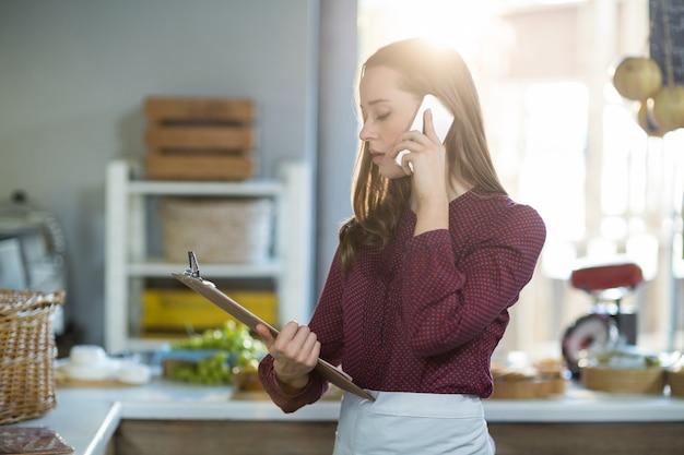 Pessoal feminino, verificando a área de transferência enquanto fala no telefone móvel no balcão