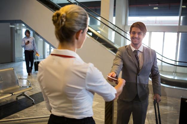 Pessoal feminino, verificando o cartão de embarque de passageiros no balcão de check-in