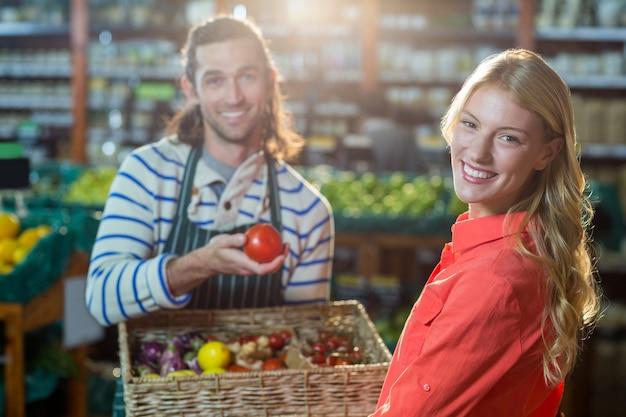 Pessoal masculino, auxiliando a mulher na seleção de legumes frescos