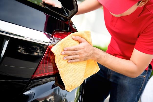 Pessoal masculino do serviço de assistência técnica que limpa a luz traseira do carro com pano de microfibra