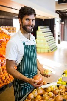 Pessoal masculino, organizar frutas na seção orgânica do supermercado