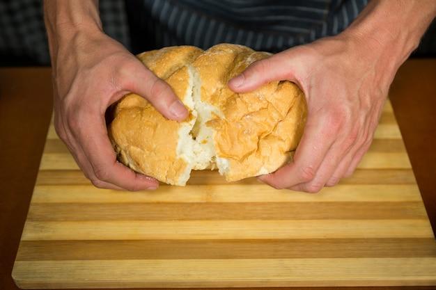 Pessoal masculino rasgando pão em padaria