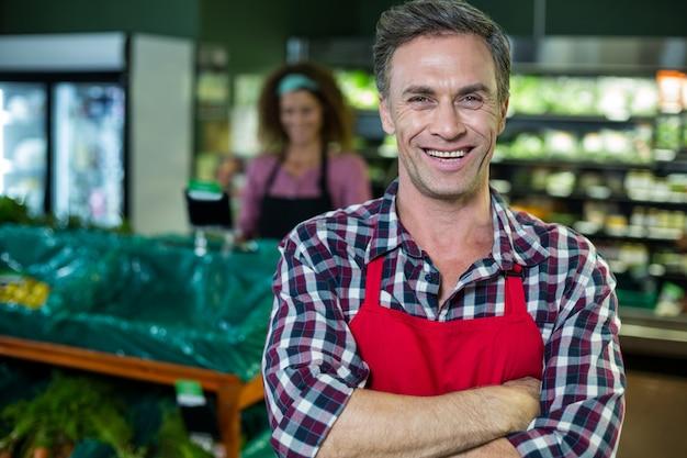 Pessoal masculino sorridente em pé com os braços cruzados na seção orgânica