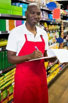 Pessoal masculino sorridente, escrevendo no bloco de notas no super mercado