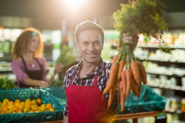 Pessoal masculino sorridente segurando o monte de cenouras na seção orgânica