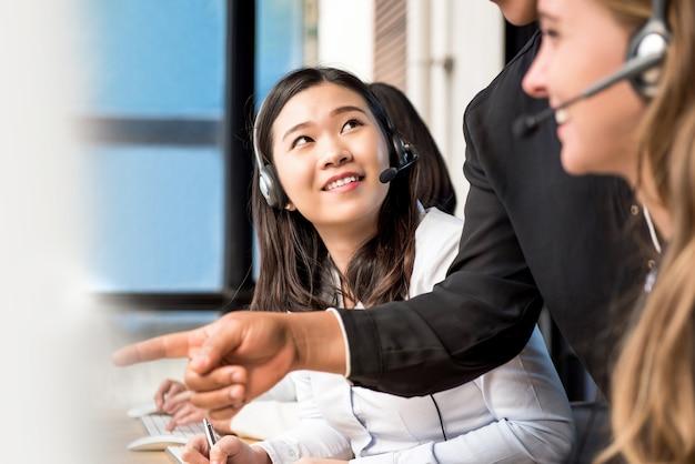 Pessoal mulher sendo treinado pelo supervisor em call center