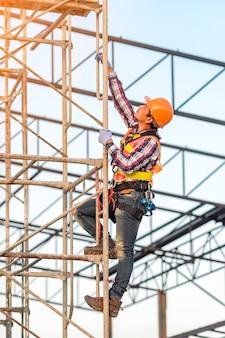 Pessoal uniformizado de acordo com as normas de segurança está subindo no andaime para ver as obras no canteiro de obras
