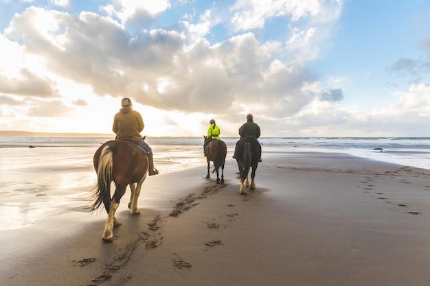 Pessoas a cavalo na praia