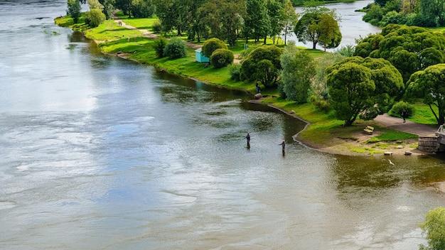 Pessoas à distância pescando em um lindo rio cheio de vegetação na costa.