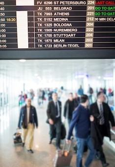 Pessoas à espera de atualizações na tela do vôo