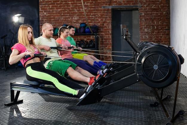 Pessoas a fazer exercícios nas máquinas de remo