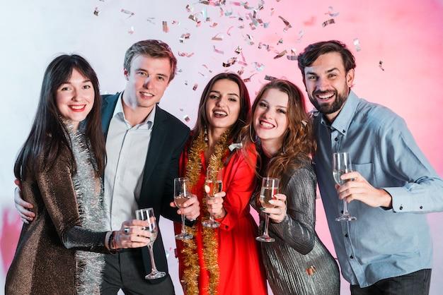 Pessoas abraçando e brindando com taças de champanhe