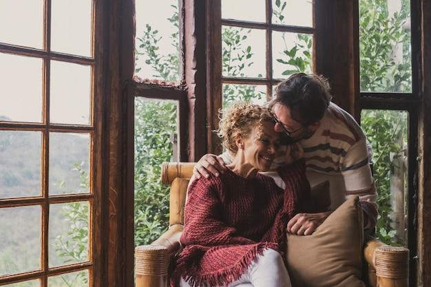 Pessoas adultas felizes no estilo de vida rural se beijando e se amando. mulher sentada no sofá e o homem a beija com ternura. outono ou inverno vida ao ar livre