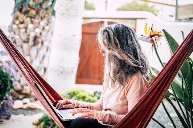 Pessoas adultas modernas alternativas em atividade de trabalho inteligente ao ar livre em casa no jardim