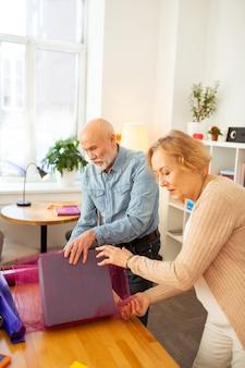 Pessoas agradáveis de cabelos grisalhos curtindo seu trabalho em equipe enquanto empacotam presentes juntos