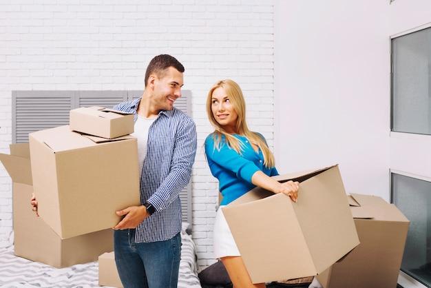 Pessoas alegres com caixas em casa nova
