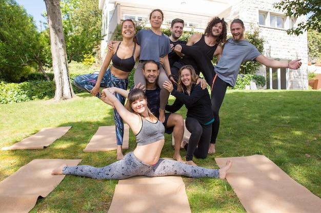Pessoas alegres da equipe de ioga posando ao ar livre