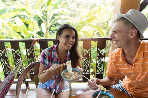 Pessoas alegres, degustação de macarrão asiático comendo